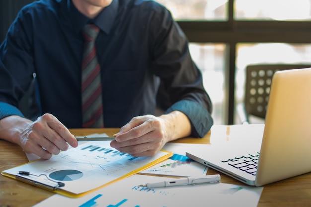 Documentos empresariais na tabela de escritório e negócios de gráficos com o diagrama de rede social e o homem trabalhando em segundo plano. Foto gratuita