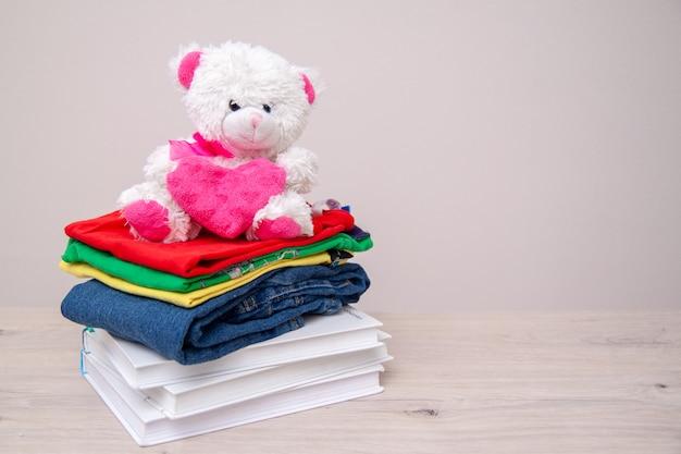 Doe mercadorias com roupas infantis, livros, material escolar e brinquedos. Foto Premium