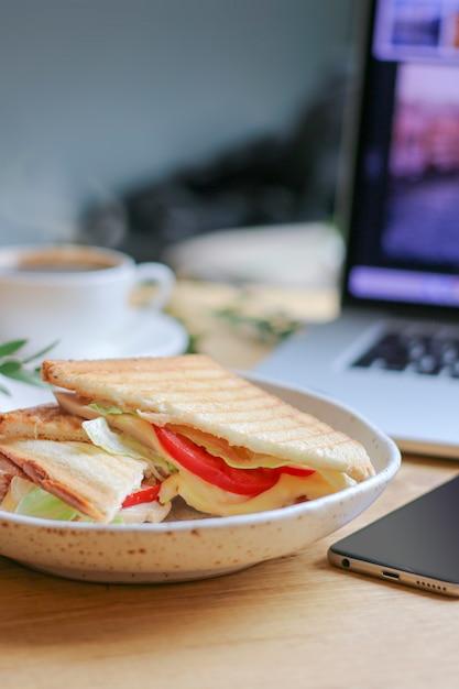Dof raso de sanduíche vegetariano com laptop e café na parte traseira turva Foto Premium