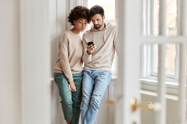 Dois alunos inter-raciais assistem atentamente ao vídeo tutorial navegando em um telefone celular moderno, aprendem o curso online, posam contra a visão doméstica perto da janela, conectados à internet 4g, leem as informações Foto gratuita
