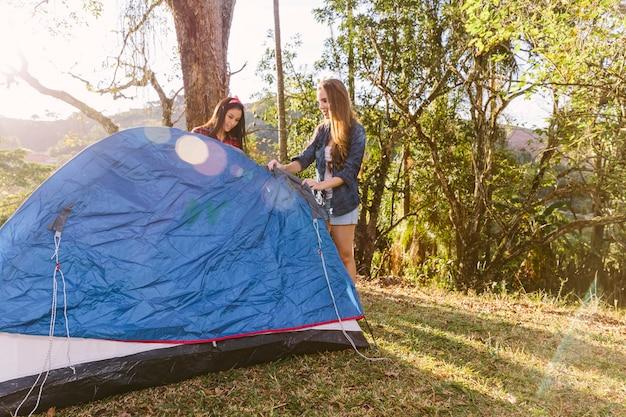 Dois, amigo feminino, preparar, barraca, durante, acampamento, viagem Foto gratuita