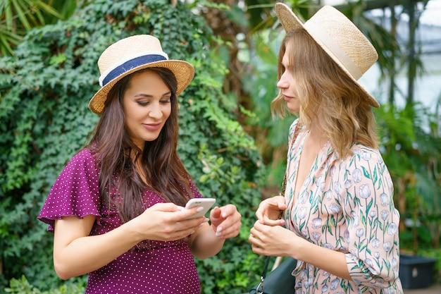 Dois amigos alegres olham para o telefone, fazem chapéus de selfie em um fundo verde natural. Foto Premium