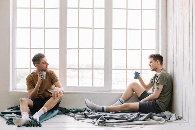 Dois amigos, café bebendo, enquanto, olhando um ao outro, sentando, perto, janela Foto gratuita