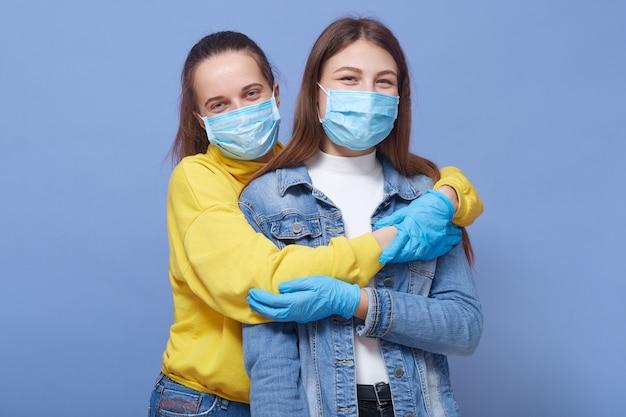 Dois amigos de bom humor, usando máscaras e máscaras médicas Foto gratuita