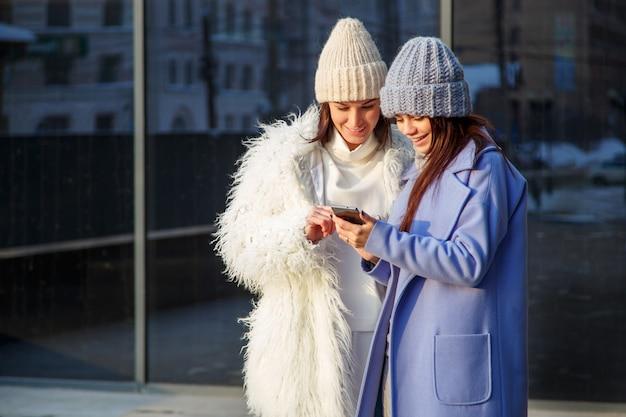 Dois amigos de mulheres engraçadas rindo e compartilhando vídeos de mídia social em um telefone inteligente ao ar livre Foto Premium