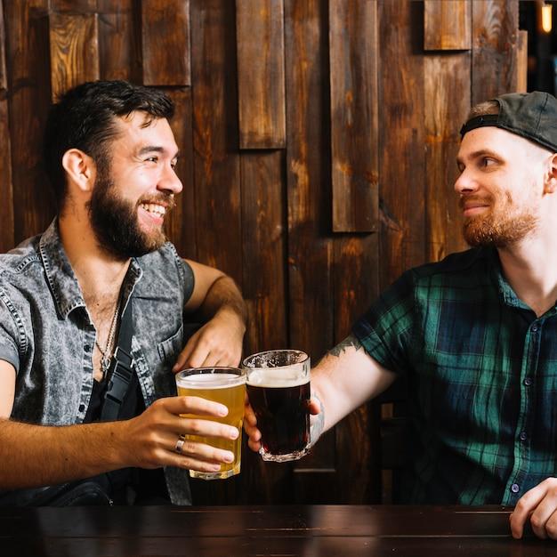Dois amigos do sexo masculino torcendo com copos de bebidas alcoólicas Foto gratuita