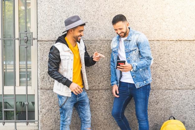 Dois amigos do sexo masculino usando telefone celular ao ar livre enquanto sorrindo. Foto Premium