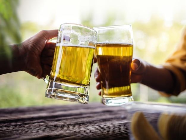 Dois amigos fazendo elogios com óculos e bebendo cerveja na varanda no verão Foto Premium