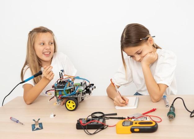 Dois amigos fazendo experimentos científicos com um carro robótico Foto gratuita