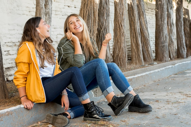 Dois amigos felizes, compartilhando o fone de ouvido para ouvir música Foto gratuita