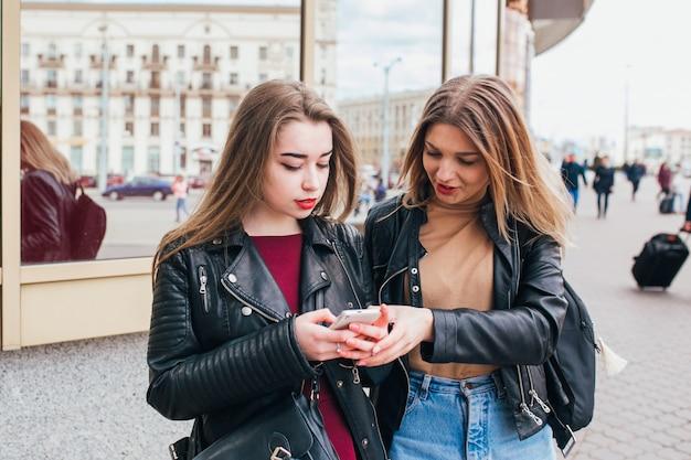 Dois amigos felizes mulheres compartilhando mídias sociais em um telefone inteligente ao ar livre na cidade. duas mulheres jovens com telefone móvel falando Foto Premium