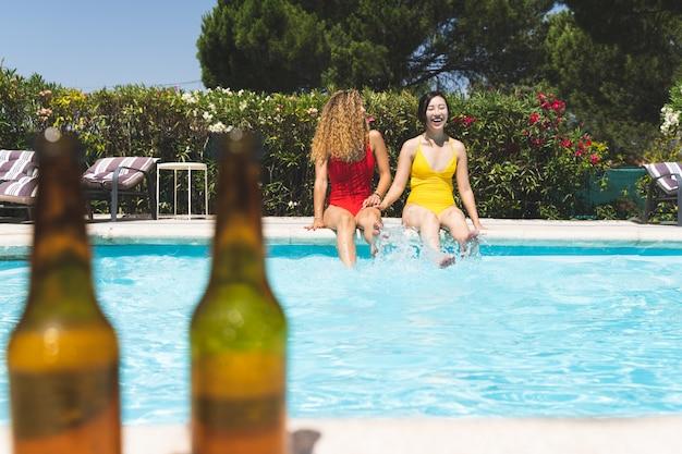 Dois amigos fêmeas que têm o divertimento na piscina. Foto Premium