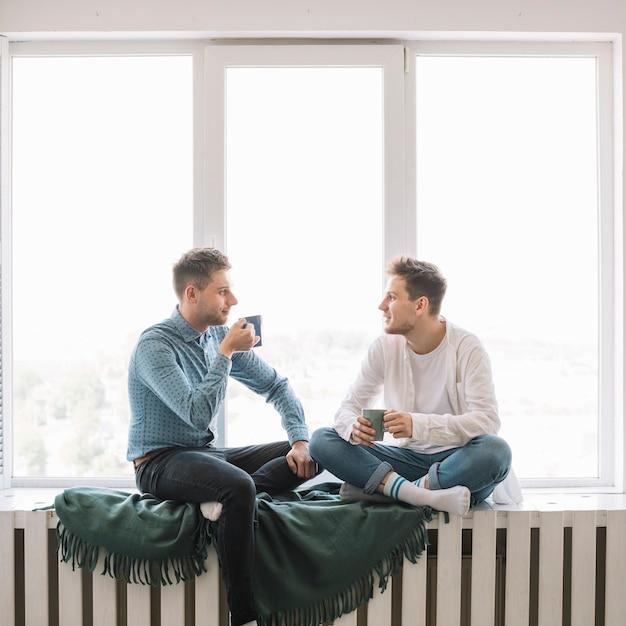 Dois, amigos jovens, discutir, um ao outro, xícara café segurando, sentando, perto, janela Foto gratuita