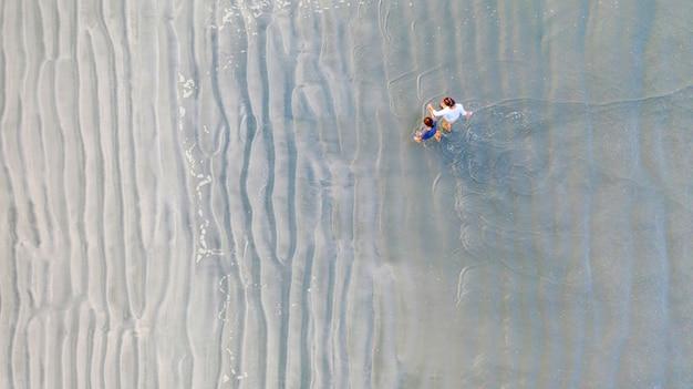 Dois, amigos jovens, ou, dois, irmãs, segurar, um ao outro, mãos, e, andar, praia Foto Premium