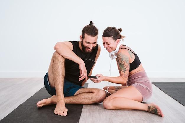 Dois amigos na academia ouvindo música no celular e fone de ouvido e se divertindo Foto Premium