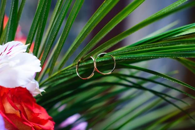 Dois anéis de casamento de ouro pendurar nas folhas de um buquê Foto Premium