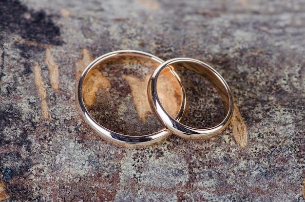 Dois anéis de casamento de ouro sobre fundo de madeira Foto Premium