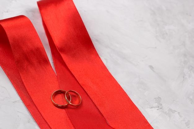 Dois anéis de ouro e decoração de casamento de fita de cetim vermelho ou conceito de fundo de convite de casamento Foto Premium