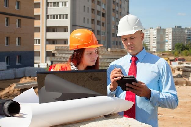 Dois arquitetos em frente ao local de construção Foto gratuita