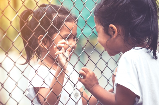 Dois, asian, crianças, falando, um ao outro, e, passe segurar, malha aço, em, cor vintage, tom Foto Premium