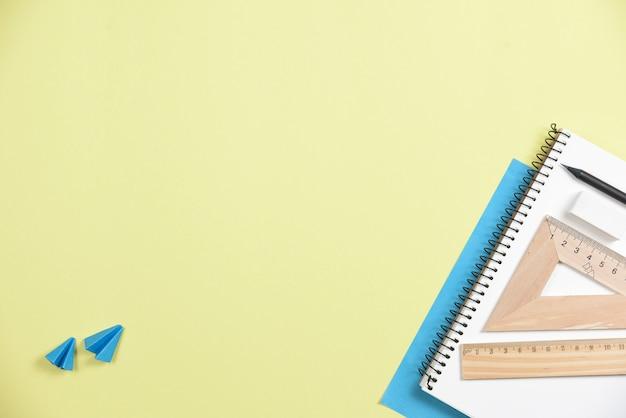 Dois aviões de origami com papelaria de escritório contra fundo amarelo Foto gratuita