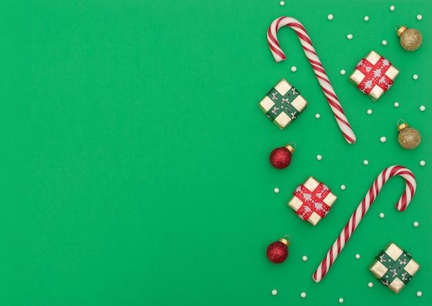 Dois bastões de natal com caixas de presente, bolas de natal vermelhas e douradas e miçangas sobre fundo verde. estilo liso leigo com espaço de cópia. Foto Premium