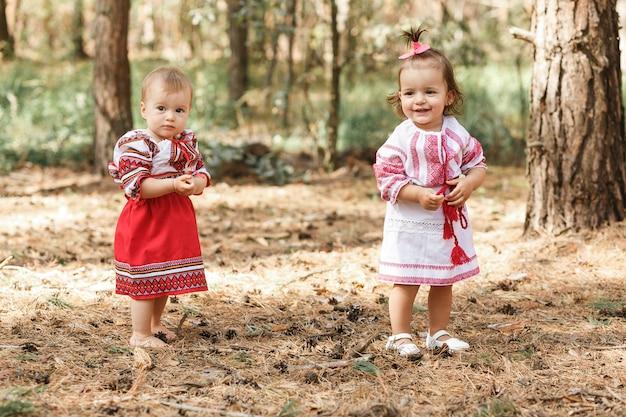 Dois bebés em ucraniano tradicional vestidos jogando na floresta de primavera. Foto gratuita