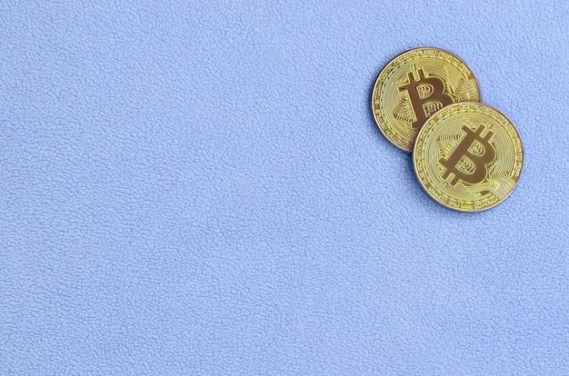 Dois bitcoins dourados encontram-se em um cobertor feito de tecido de lã azul claro macio e fofo Foto Premium