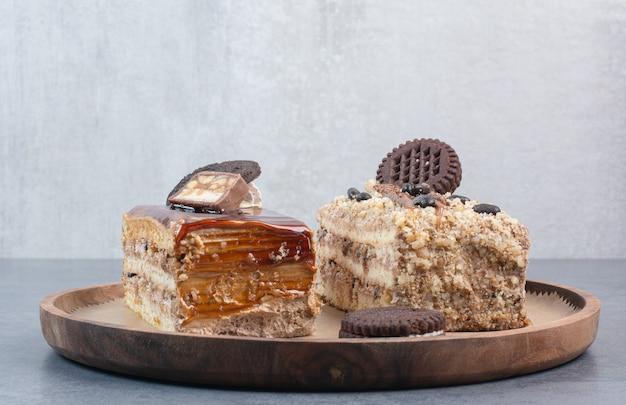 Dois bolos deliciosos doces com biscoitos na placa de madeira. Foto gratuita