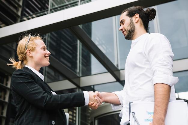 Dois, businesspeople, ficar, exterior, escritório, predios, apertar mão Foto gratuita