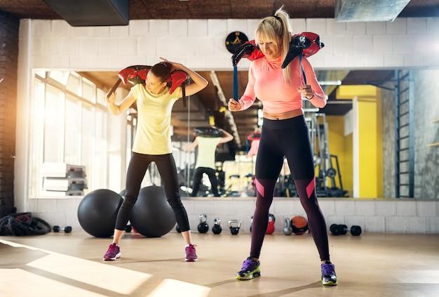 Dois cabem garotas fortes em uma academia, preparando-se para um treinamento com pesos. Foto Premium