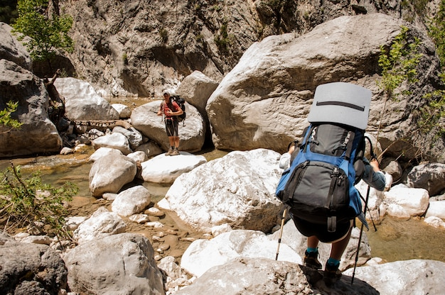 Dois caminhantes viajando pelo desfiladeiro com mochilas Foto Premium