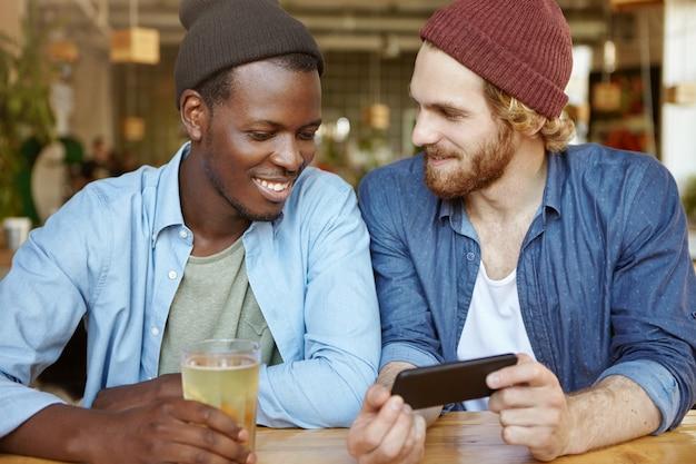 Dois caras de diferentes raças, bebendo cerveja no pub. cara branco de aparência moderna, com barba grossa, tendo uma boa conversa com seu amigo Foto gratuita