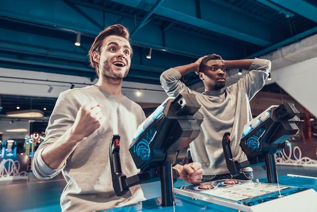 Dois caras pilotar naves azuis na arcada Foto Premium