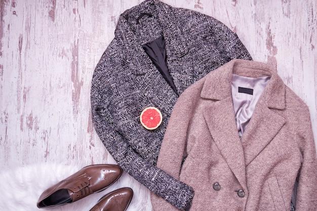 Dois casaco de lã, sapatos de couro marrom com um pêlo branco, metade de uma toranja, um fundo de madeira. conceito de moda. vista do topo Foto Premium