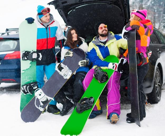 Dois casais se divertindo e praticando snowboard Foto gratuita