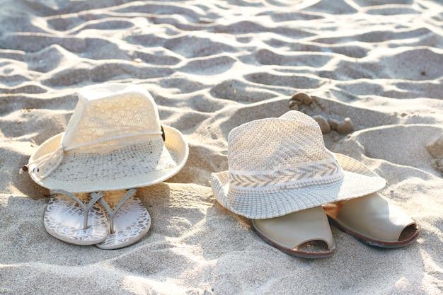 Dois chapéus e sandálias deitar na areia Foto Premium