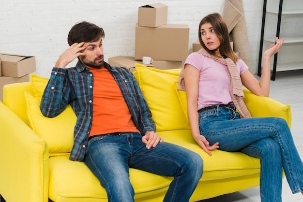 Dois, chateado, par jovem, sentar sofá amarelo, em, seu, casa nova Foto gratuita