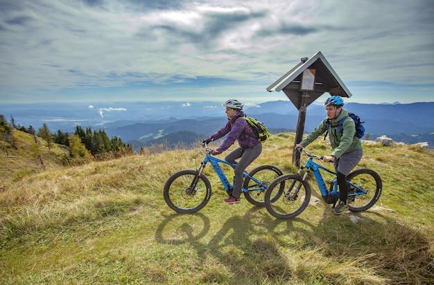 Dois ciclistas no pico de uma montanha com um belo ambiente Foto gratuita