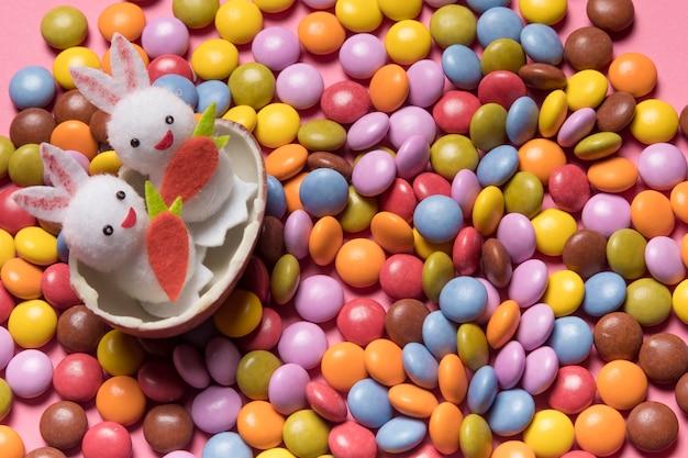 Dois coelhos bonitos dentro do ovo de páscoa quebrado sobre os doces de gema colorido Foto gratuita