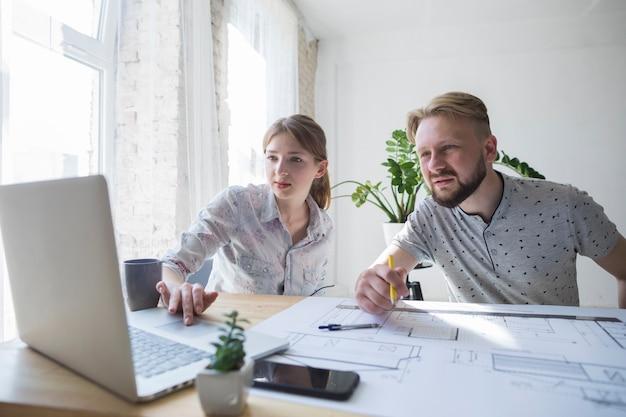 Dois, colega trabalho, olhar, laptop, enquanto, trabalhando, em, escritório Foto gratuita