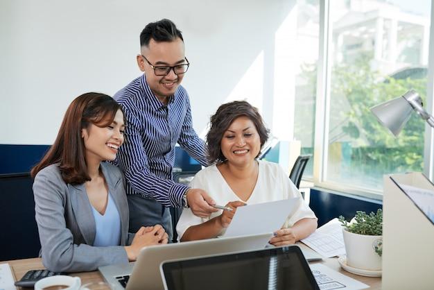 Dois colegas asiáticos feminino e um masculino discutindo documento juntos no escritório Foto gratuita