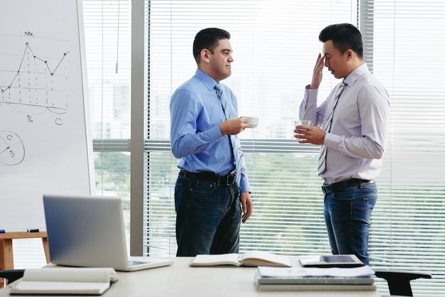 Dois colegas de trabalho discutindo a carga de trabalho na xícara de café Foto gratuita