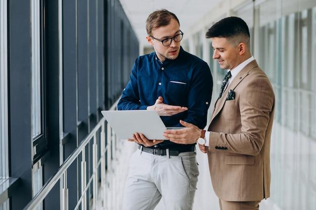 Dois colegas do sexo masculino no escritório, em pé com o laptop Foto gratuita