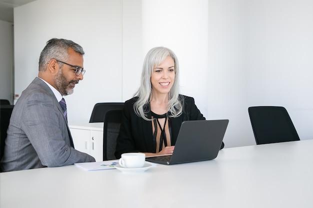 Dois colegas felizes usando laptop para videochamada, sentados à mesa com uma xícara de café, olhando para a tela e conversando. conceito de comunicação online Foto gratuita
