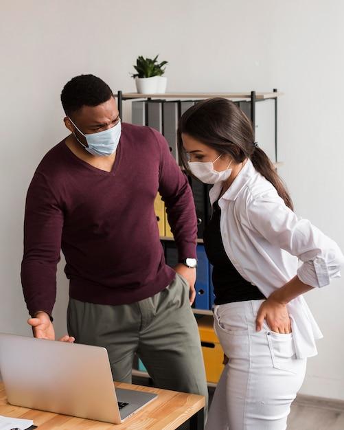 Dois colegas que trabalham no escritório durante a pandemia com máscaras Foto gratuita