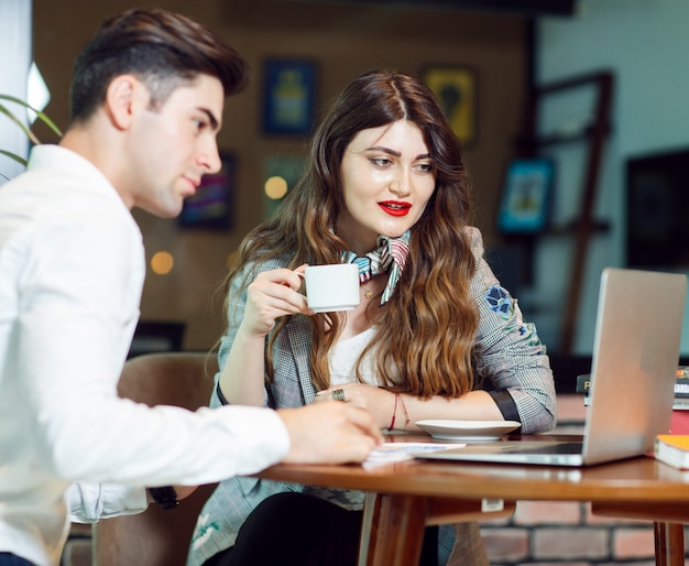 Dois colegas tendo café e verificando um projeto na zona de estar de um escritório. Foto gratuita
