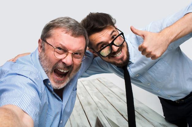 Dois colegas tirando a foto para eles auto sentado no escritório Foto gratuita