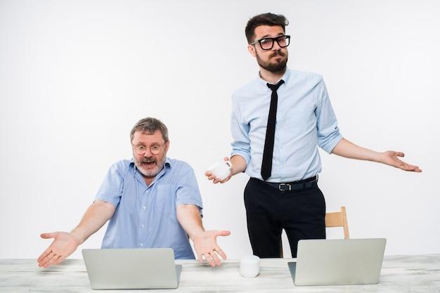 Dois colegas trabalhando juntos no escritório em branco Foto gratuita