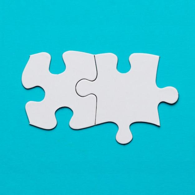 Dois conectaram a peça do quebra-cabeça branca sobre a superfície azul Foto gratuita